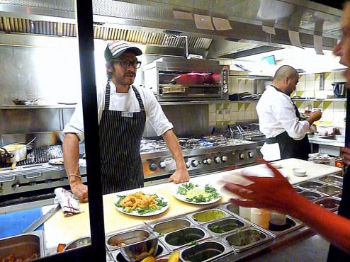 The hot kitchen is not part of the dinning room but is still open kitchen for the customers to take a peek.