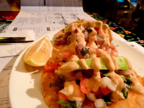 Ceviche Tostadas: two flat crispy corn tortillas with fish ceviche marinated in lemon, tomato, onion and chopped cilantro and chipotle sauce.