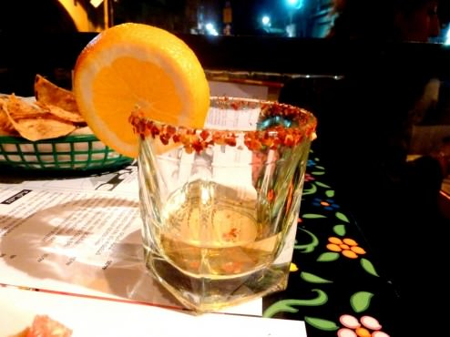 """Mescal (a type of Mexican tequila) in a glass with a chilly rim and a slice of orange (34 NIS). Omer said: """"Cool!"""""""