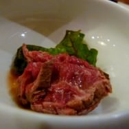 Marinated Tataki Beef with some green leaves.