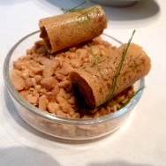 Caramel roll filled with Satay sauce, basil, lemongrass, coriander and peanuts, served on a platter of broken peanuts